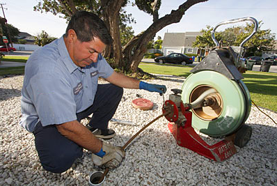 Miami Beach plumbing contractor snakes a drain line with a power auger