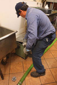 Miami Beach plumbing contractor cleans a grease trap at a Cuban restaurant